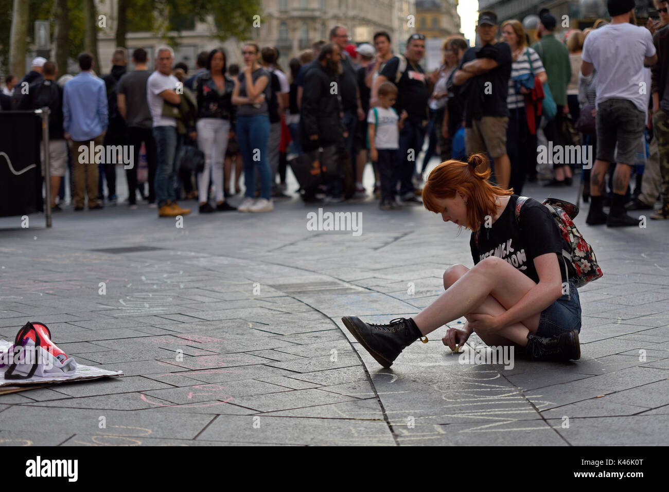 Animal rights activists protesting outside Burger King in Leicester Square, London. Female activist chalking slogans onto the pavement. Space for copy - Stock Image
