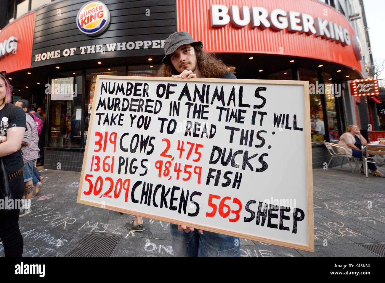 Animal rights activists protesting outside Burger King in Leicester Square, London. Shock tactics placard - Stock Image