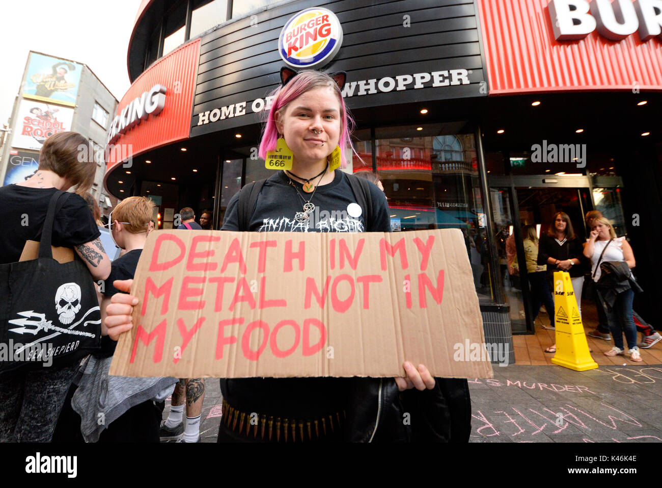 Animal rights activists protesting outside Burger King in Leicester Square, London. Reference to death metal music. Female activist - Stock Image