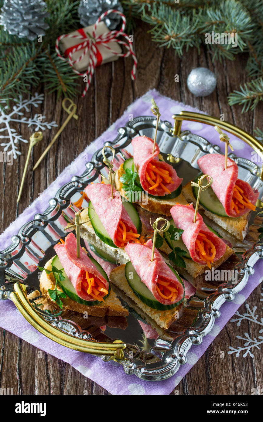 Appetizer canape on crispy bread with cucumber, carrots and sausage. Beautiful Christmas and New Year's food background. Selective focus. - Stock Image