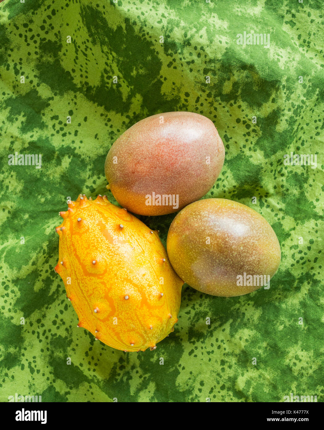 passion fruit and kiwano melon isolated on a green cloth viewed from above - Stock Image