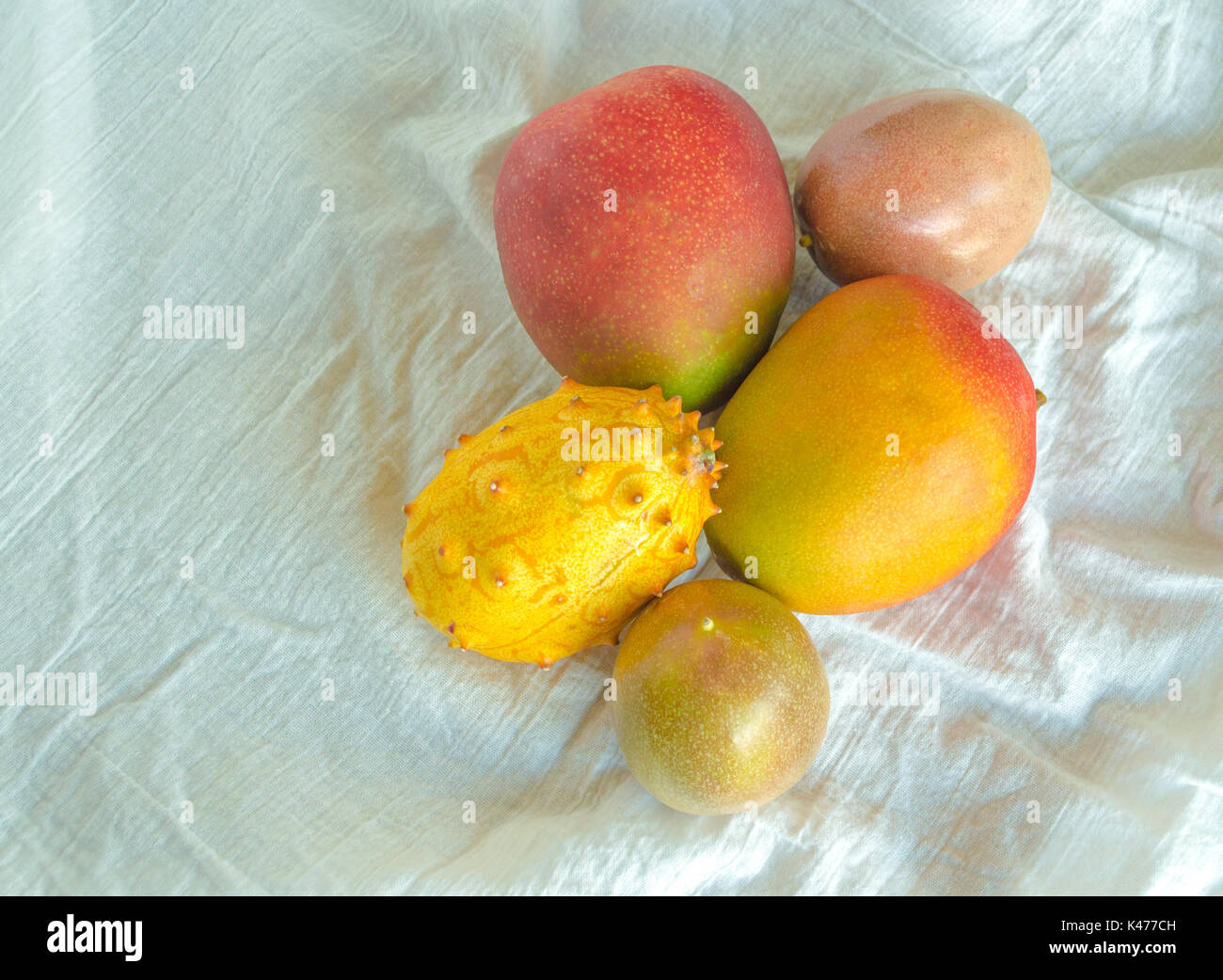 mangoes, passion fruit and melon on a white cloth viewed from above - Stock Image