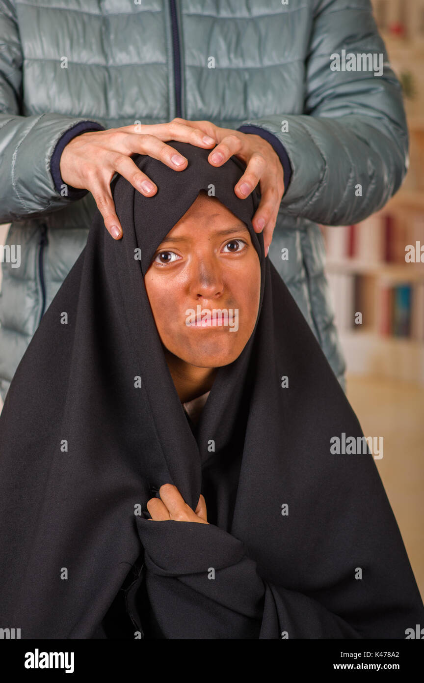 Portrait of a muslim girl wearing a hijab with a white man behind her using both hands oppressing her head in a blurred background