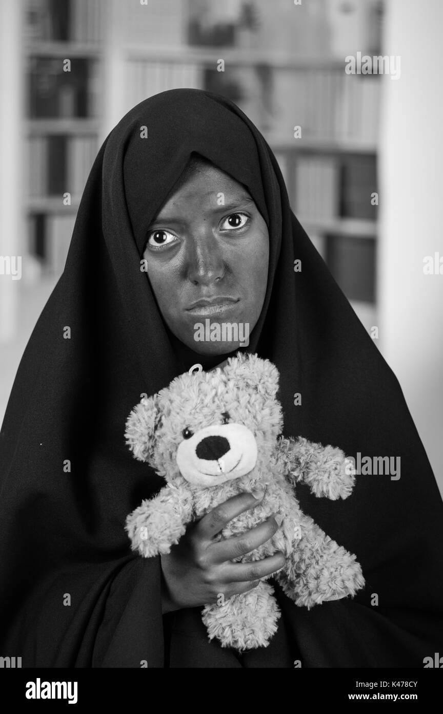 Portrait of a sad muslim girl wearing a hijab and holding her arms her teddy bear