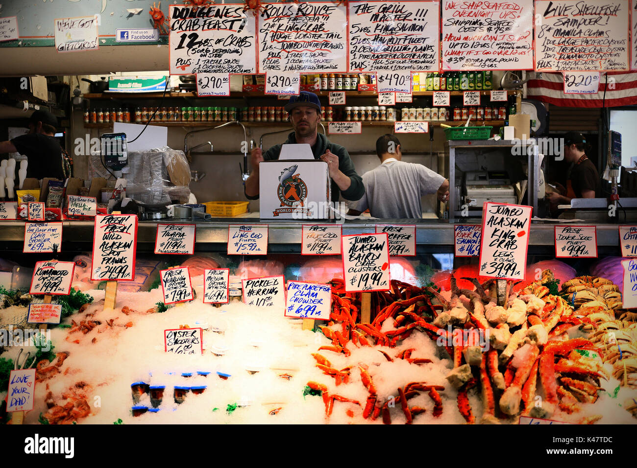 SEATTLE, WA, USA - JUNE 2016 - Unidentified seller at the Pike Fish Market. Prices and merchandise at the front. - Stock Image
