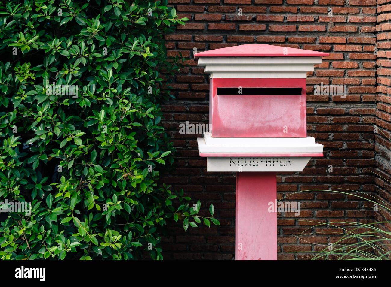 Outbox outside the house with bushes and orange brick walls. - Stock Image