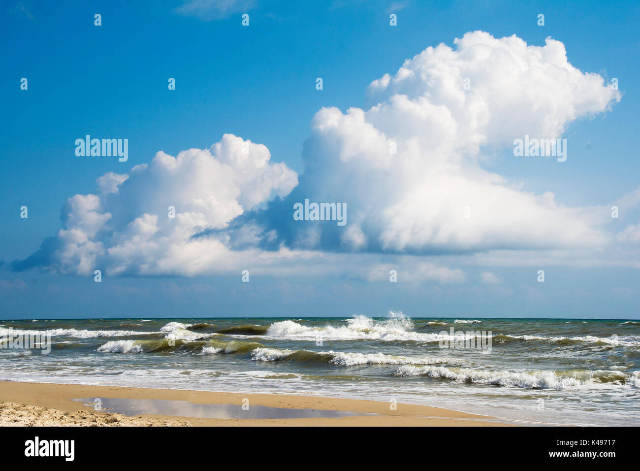 Bright blue sky with clouds over stormy sea - Stock Image