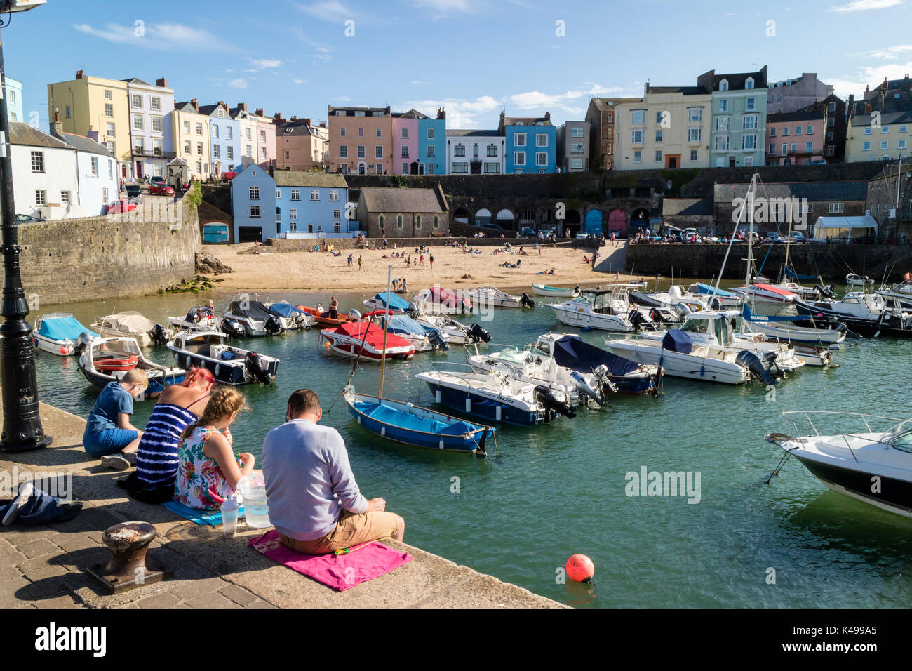 A family on holiday looking over colourful, pretty houses near harbour at Tenby, Pembrokeshire, Wales - Stock Image