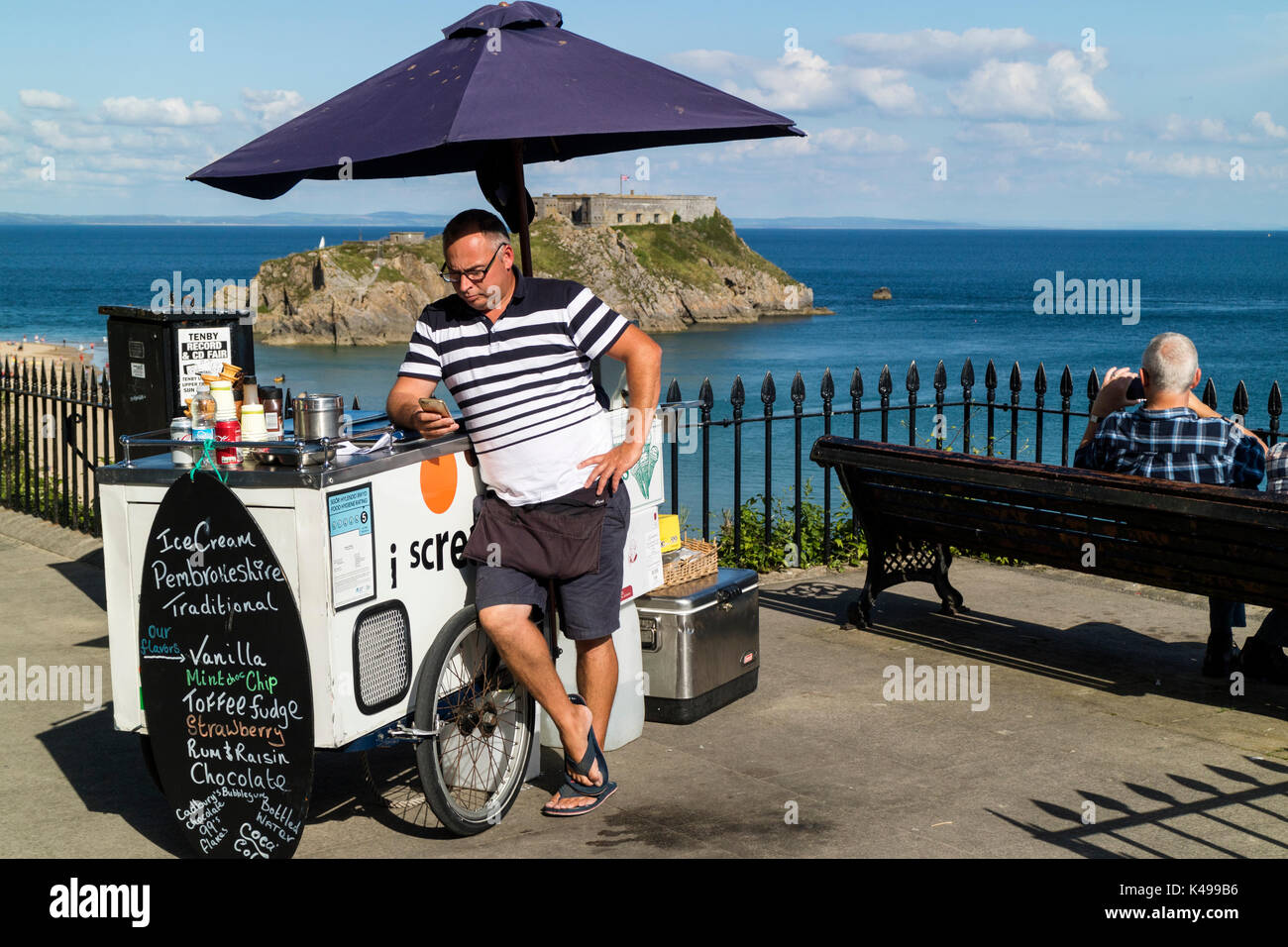 A man selling ice cream from a bicycle on the sea front in Tenby, Wales checks his mobile / cell phone with St Catherine's Island in background - Stock Image