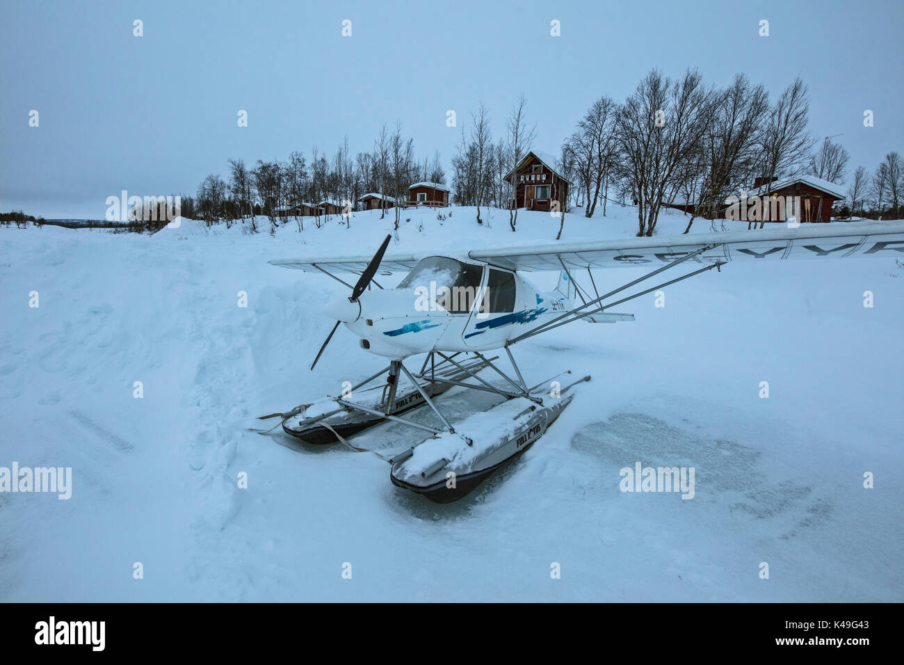 Hydroplane on the icy ground frames the wooden huts covered with snow Ruka Kuusamo Ostrobothnia region Lapland Finland Europe - Stock Image