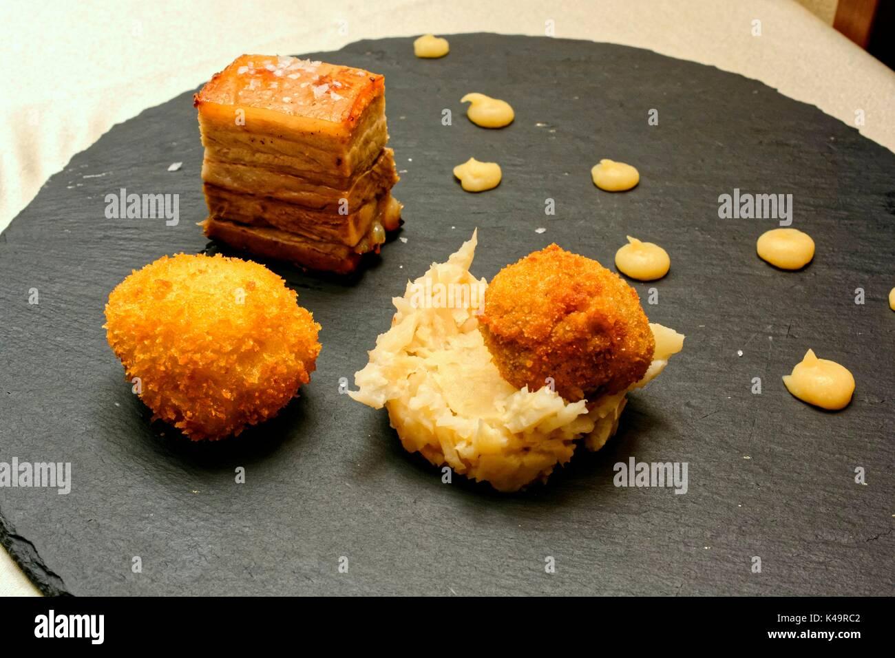 Fine Dining, Crispy Pork Belly Seasoned With Quince Cream, Pureed Parsnake, Breaded Potato Dumpling And Pork Paste - Stock Image