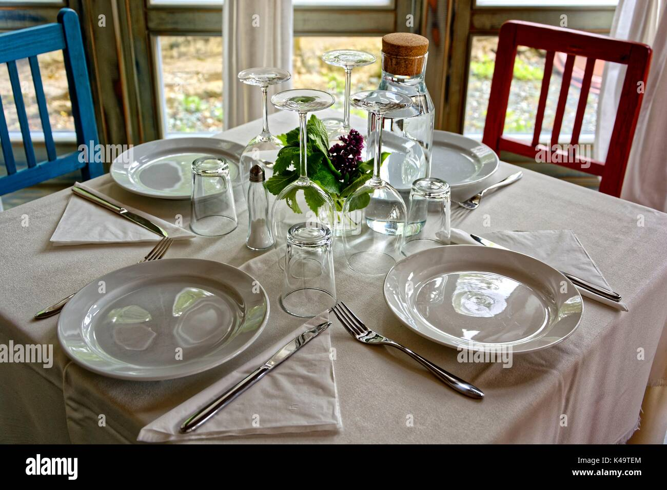 Table Set For Four Persons With Plates And Glasses - Stock Image