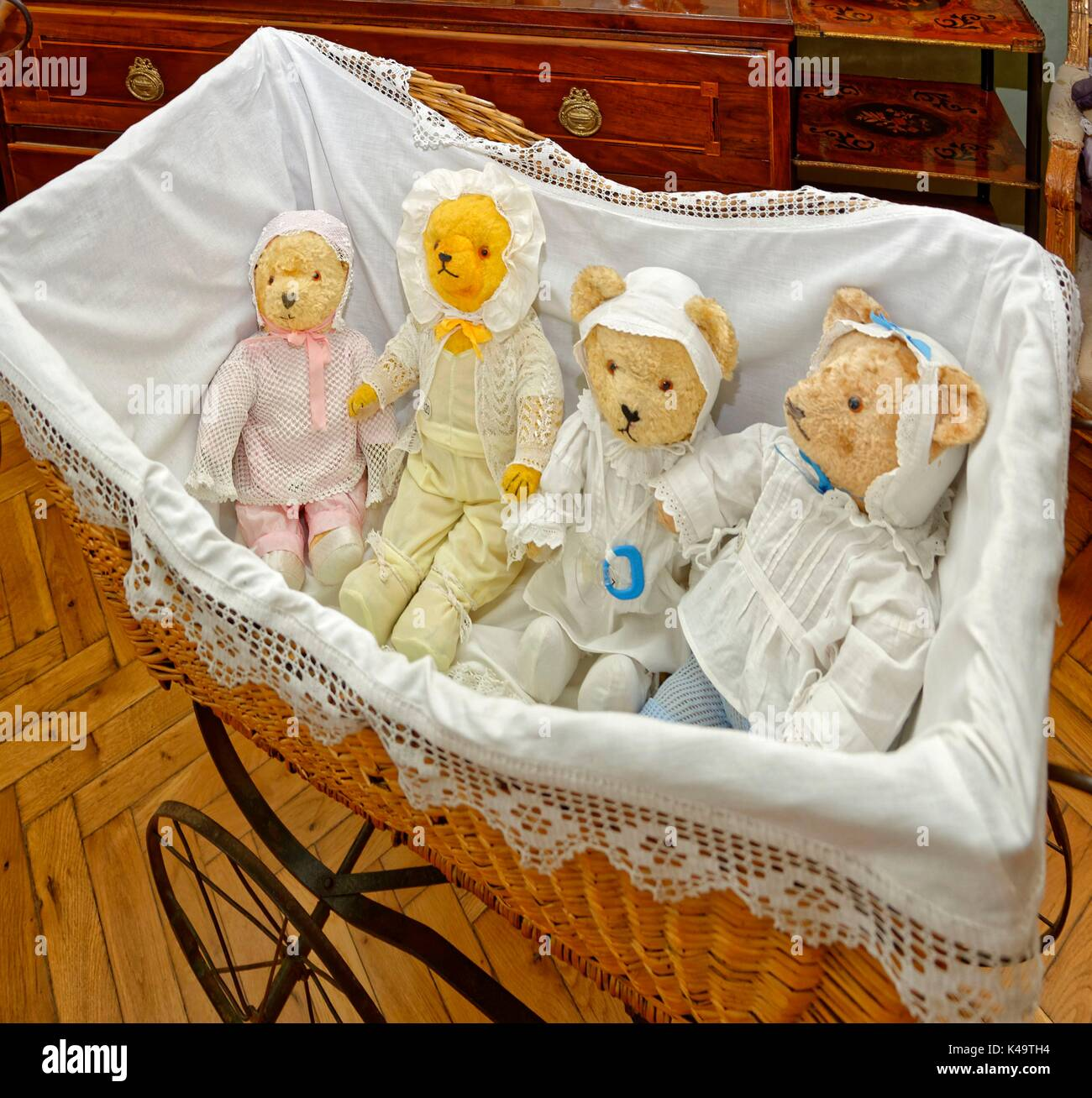 Four Teddy Bear Children In Basket Baby Carriage - Stock Image