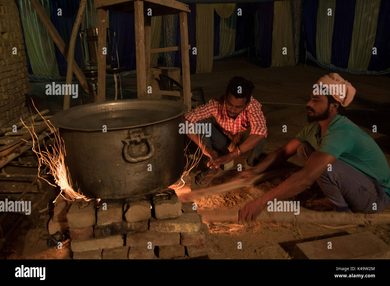 two young men stoke a fire to brew tea for a large wedding reception in Punjab, India - Stock Image