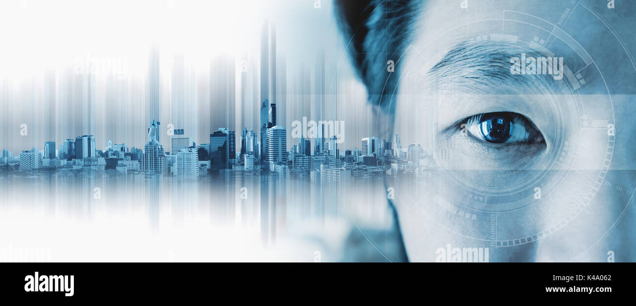 Close-up Asian businessman's eye , with futuristic technology visual effect and city hologram - Stock Image