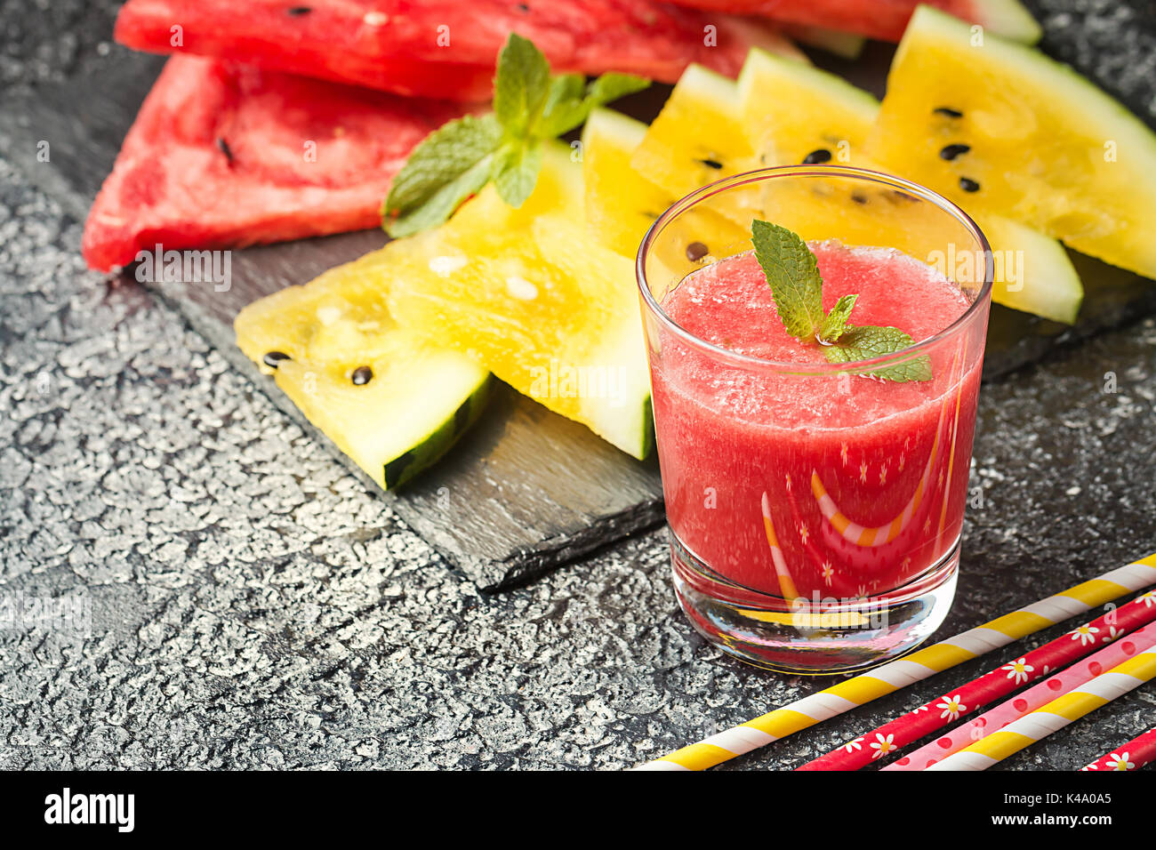Glass of fresh red watermelon juice with slices of red and yellow watermelon. Healthy eco sweet food rich in vitamins. - Stock Image