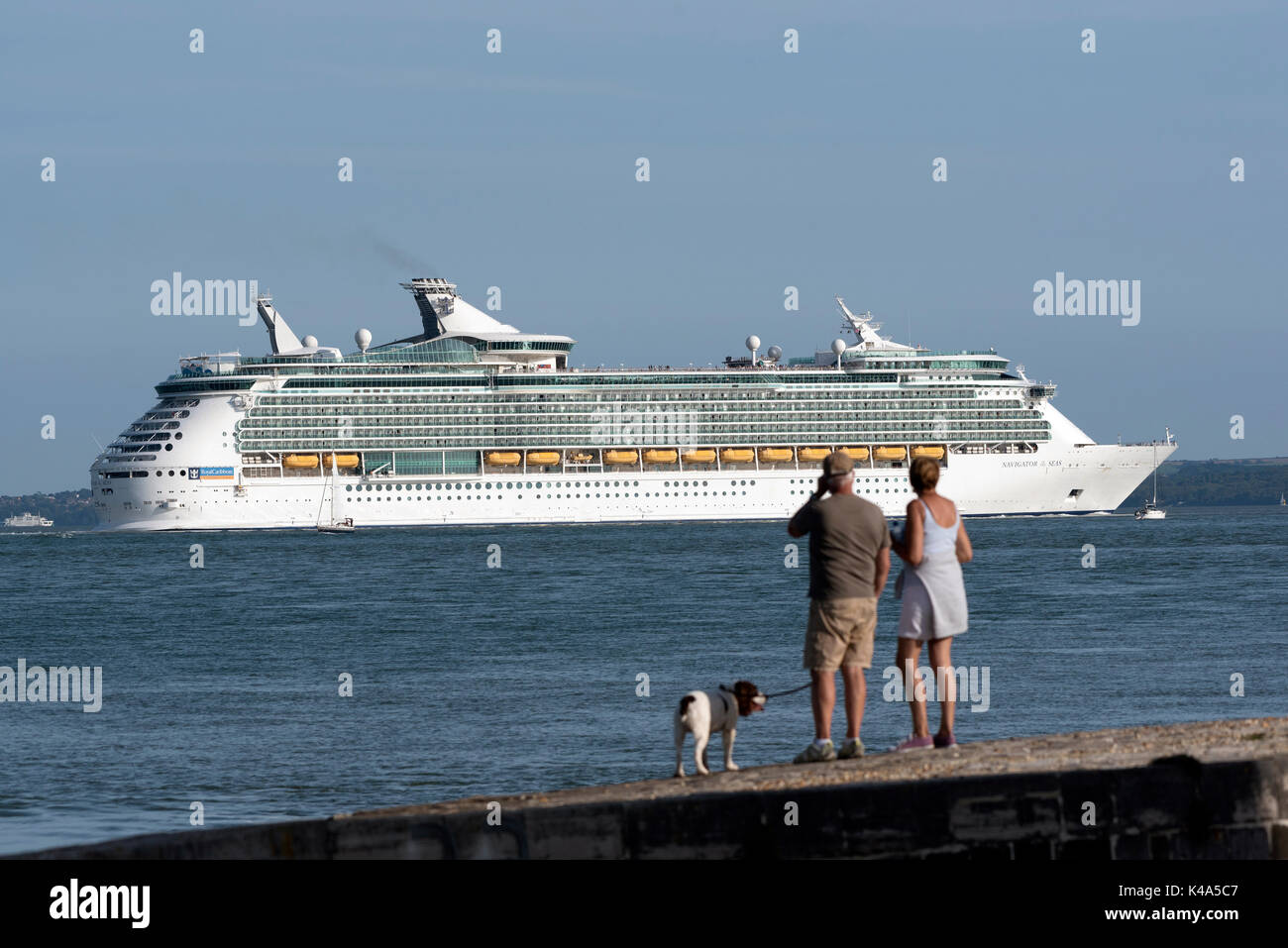 Holidaymakers watching from Calshot Spit on Southampton Water southern England UK with a backdrop of the cruise liner Navigator of the Seas. August 20 - Stock Image