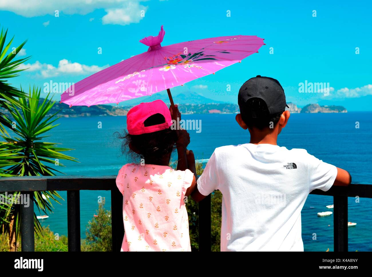 Two children enjoy viewing beautiful scenary from a clif top of Baia, Italy. - Stock Image