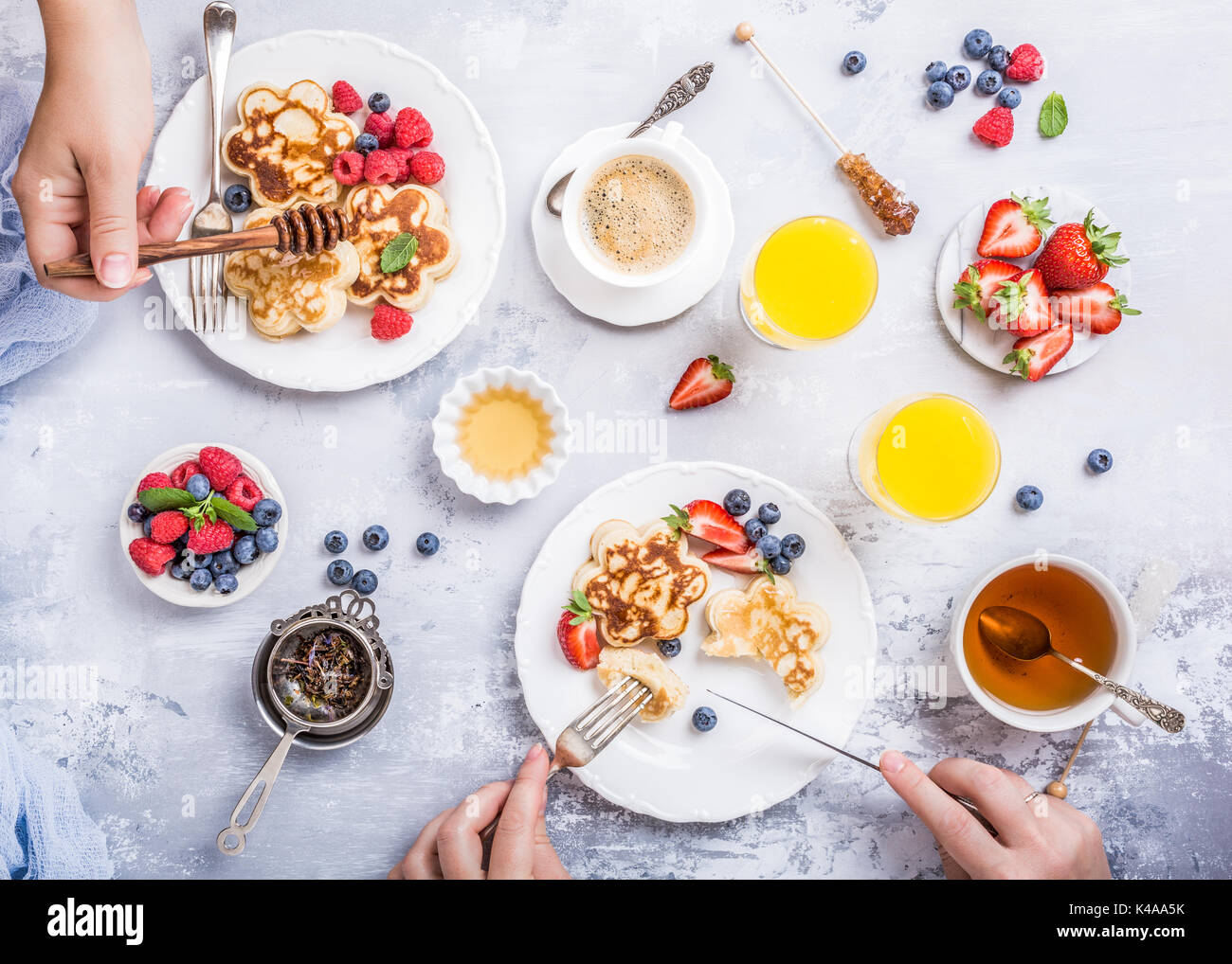 Flat lay with scotch pancakes in flower form, berries and honey with human hands. Healthy breakfast concept. Women eating together, top view. - Stock Image