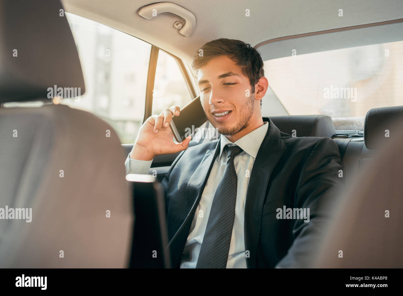 Businessman working while sitting in a car. Man beeing driven to work in his limo. Suit and tie businessman in the back seat making a call while the limo driver is driving. - Stock Image