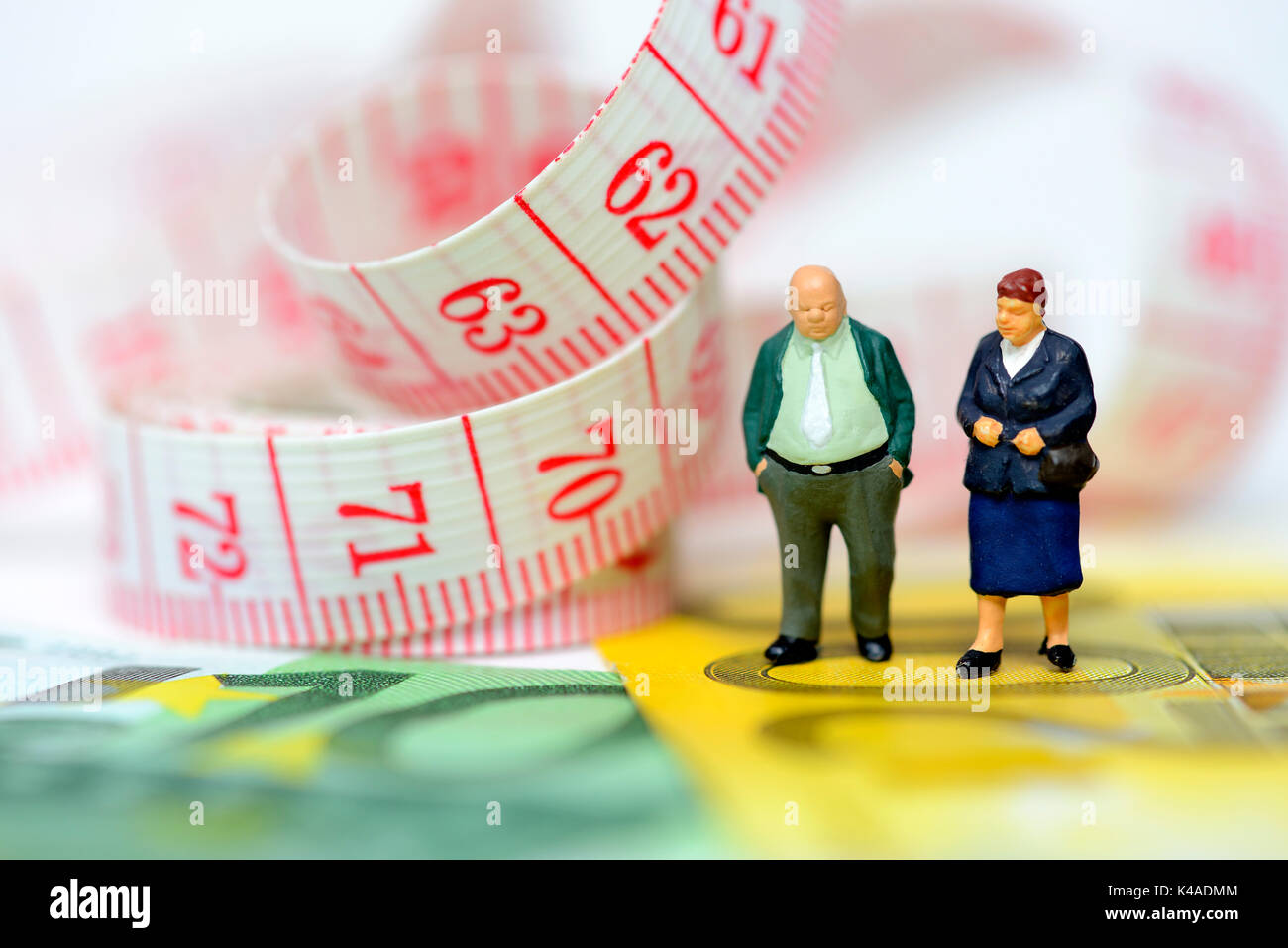 Old Couple Miniatures, Euro Banknotes And Measuring Tape Stock Photo