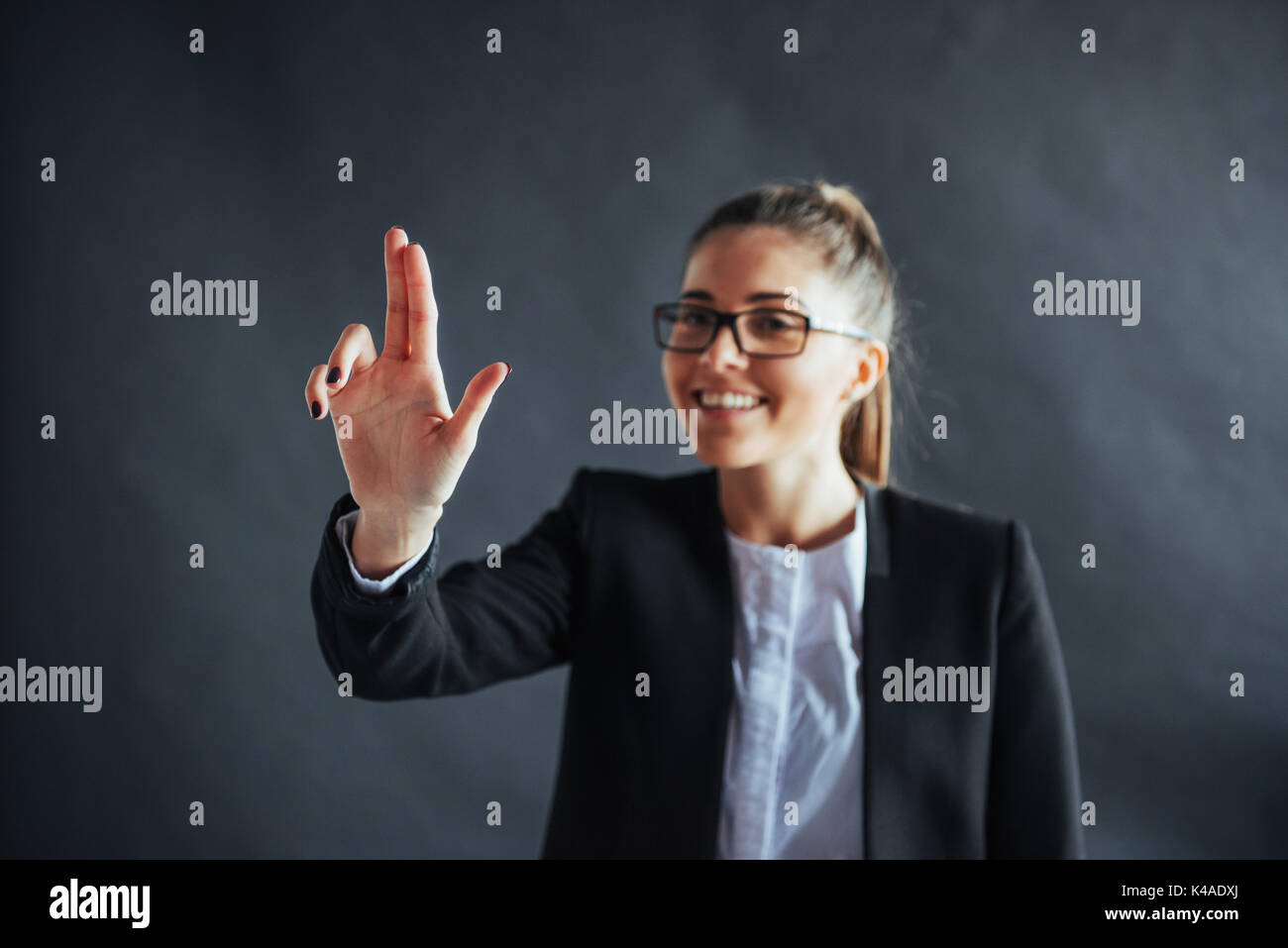 Happy business woman shows finger up, standing on a black background in the studio, friendly, smiling, focus on hand. - Stock Image