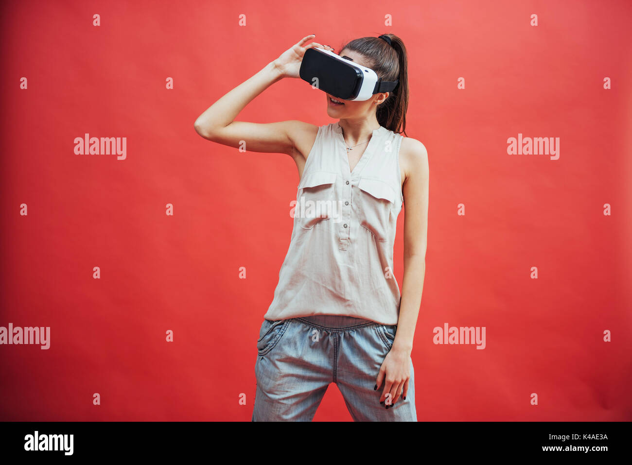 portrait of happy smiling young beautiful girl, gain experience using VR-headset virtual reality glasses, isolated - Stock Image