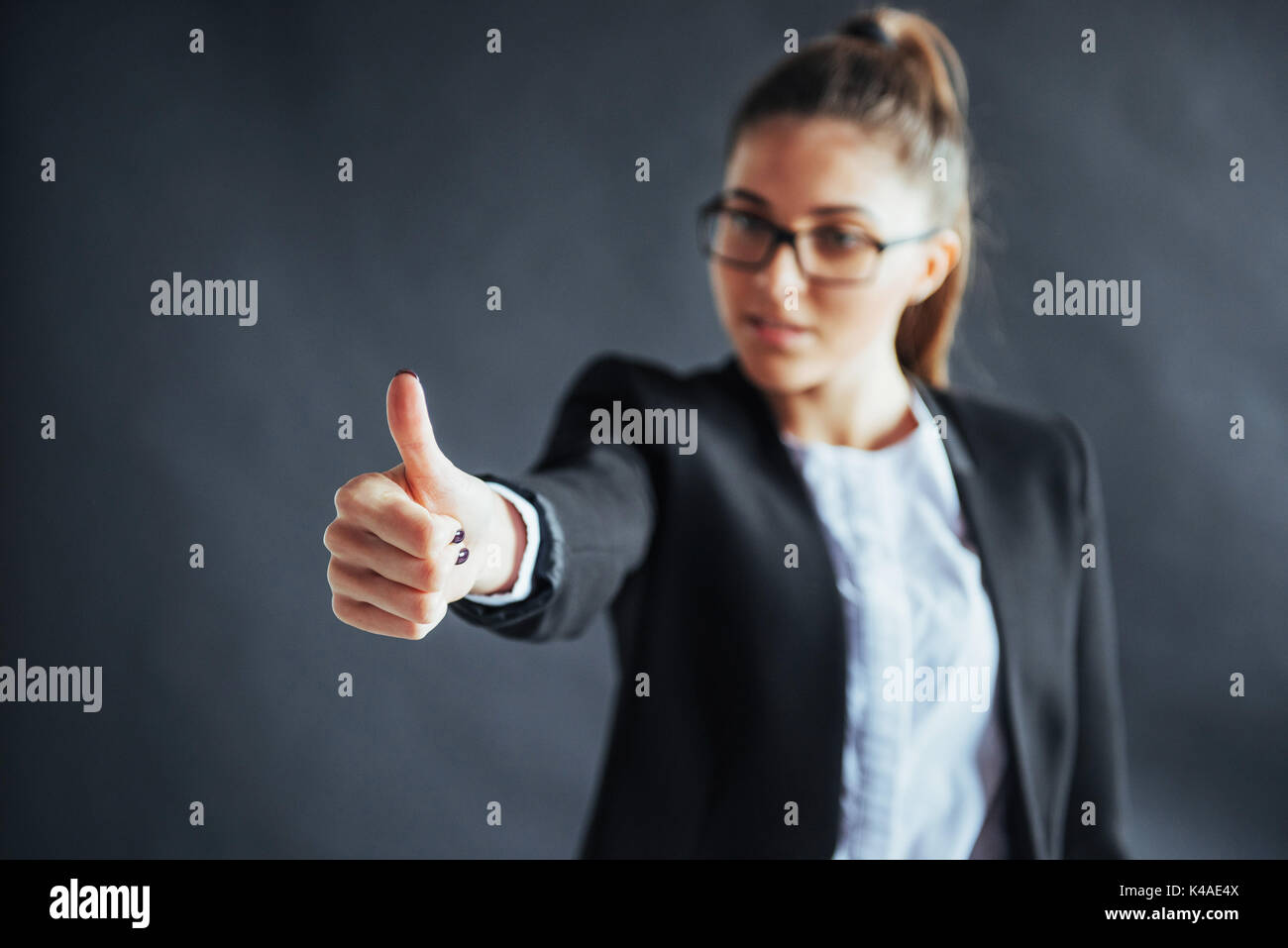 Young woman shows thumb up standing on black background, focus on hand. - Stock Image