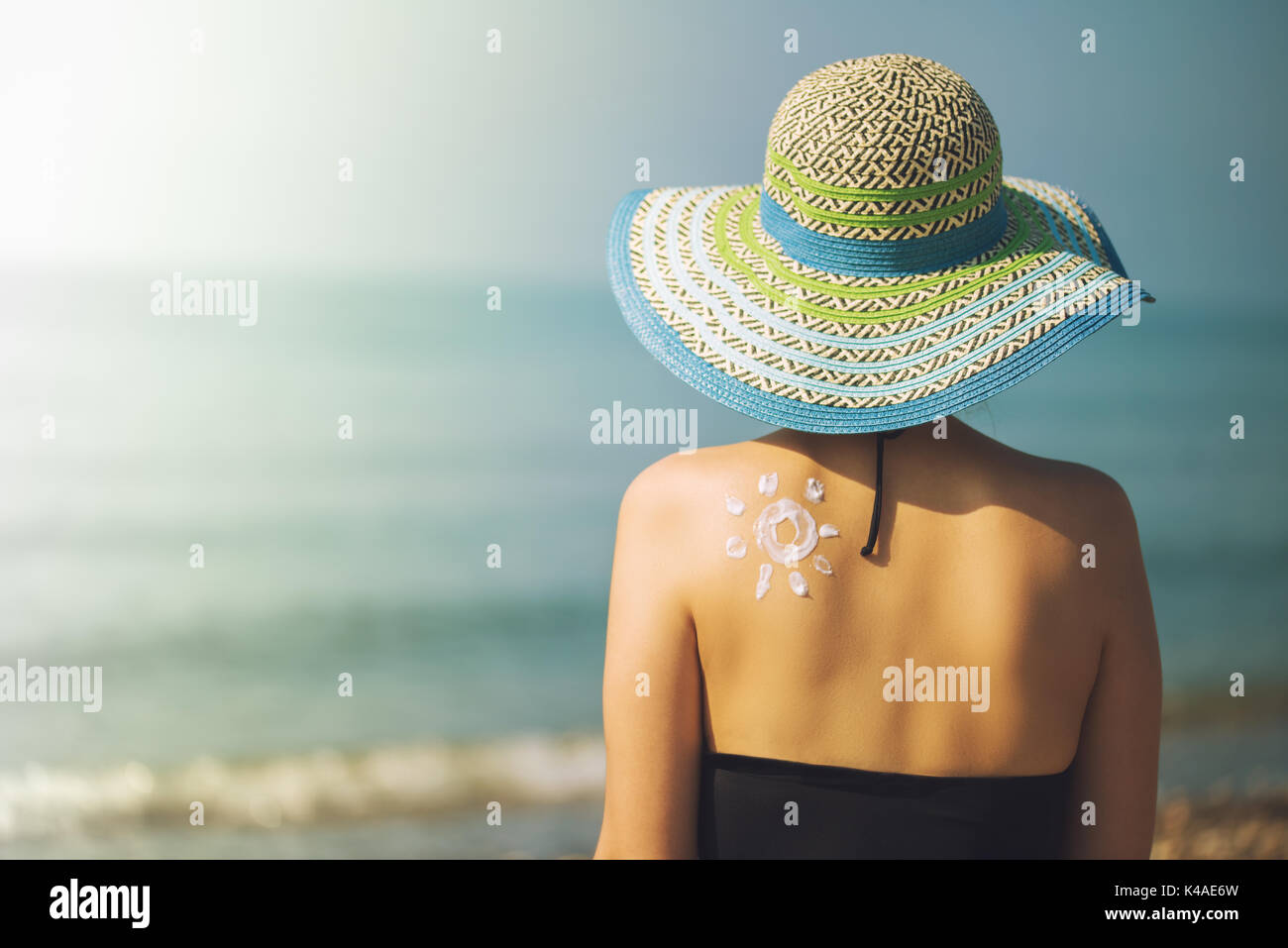 Young woman with sun shape on the shoulder holding sun cream bottle on the beach - Stock Image