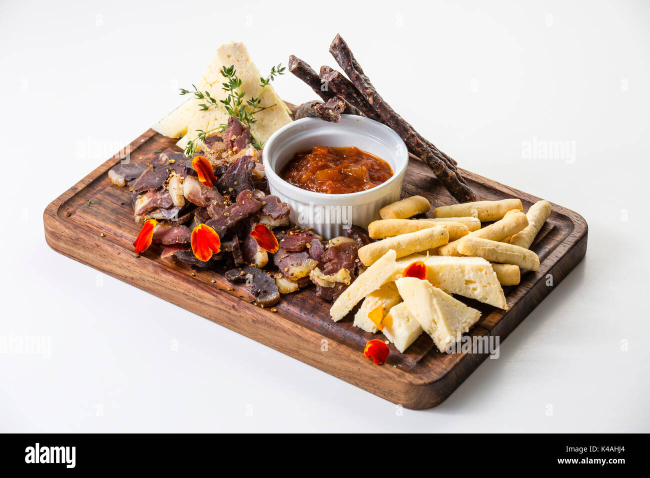 Namibian plate with biltong, dry sausage, fresh farm cheese, grissini and tomato chutney - Stock Image
