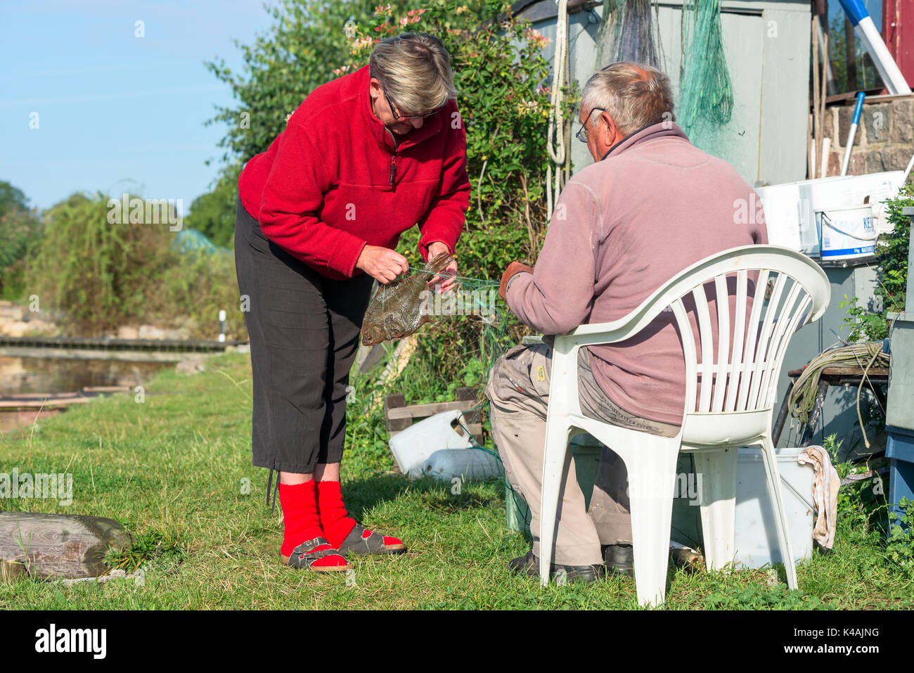 Karlskrona, Sweden - August 28, 2017: Real life documentary of coastal lifestyle. Senior couple untangling fishing nets and removing a flounder from t - Stock Image