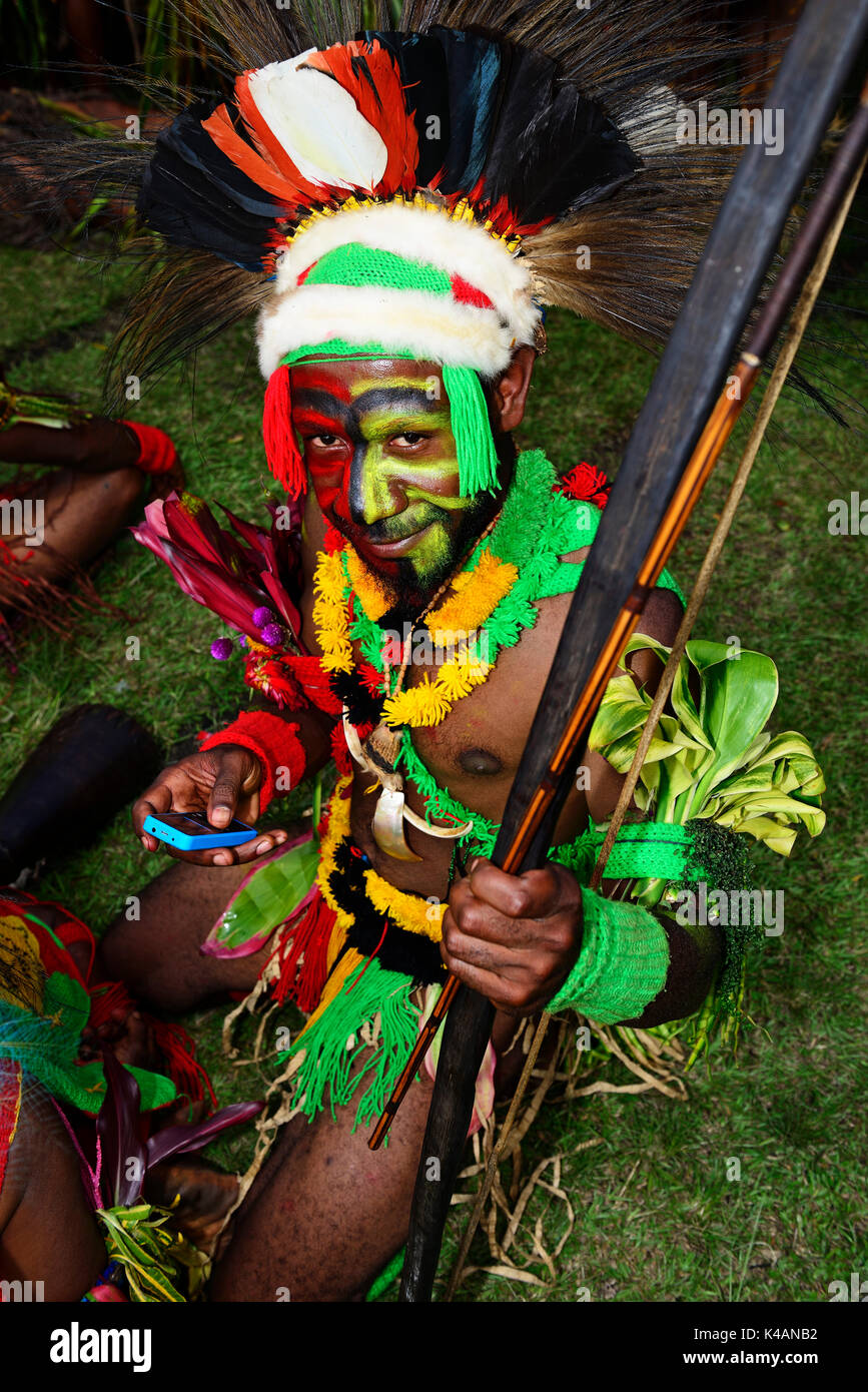 Mehiwaga warrior typing into his smartphone, the highland tribes presenting themselves at the annual Sing Sing of Goroka - Stock Image