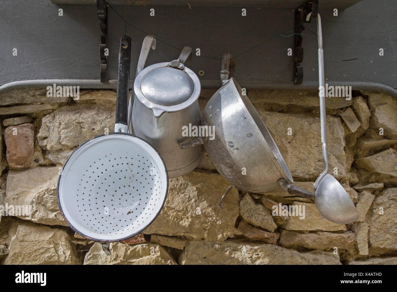 Rustic Cookware On A Stone Wall Stock Photo
