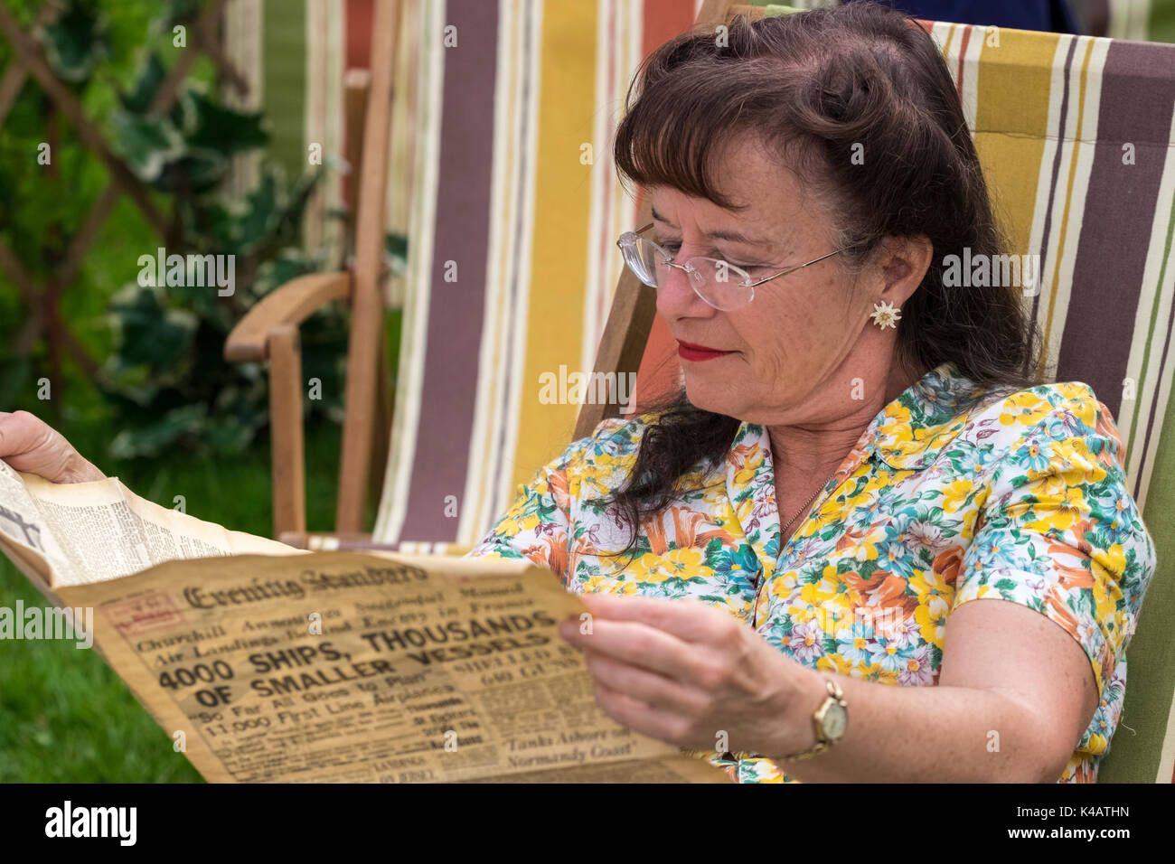 Woman at a1940's Living History camp re-enactment event reading an old copy of the Evening Standard newspaper with historical news about the period. - Stock Image