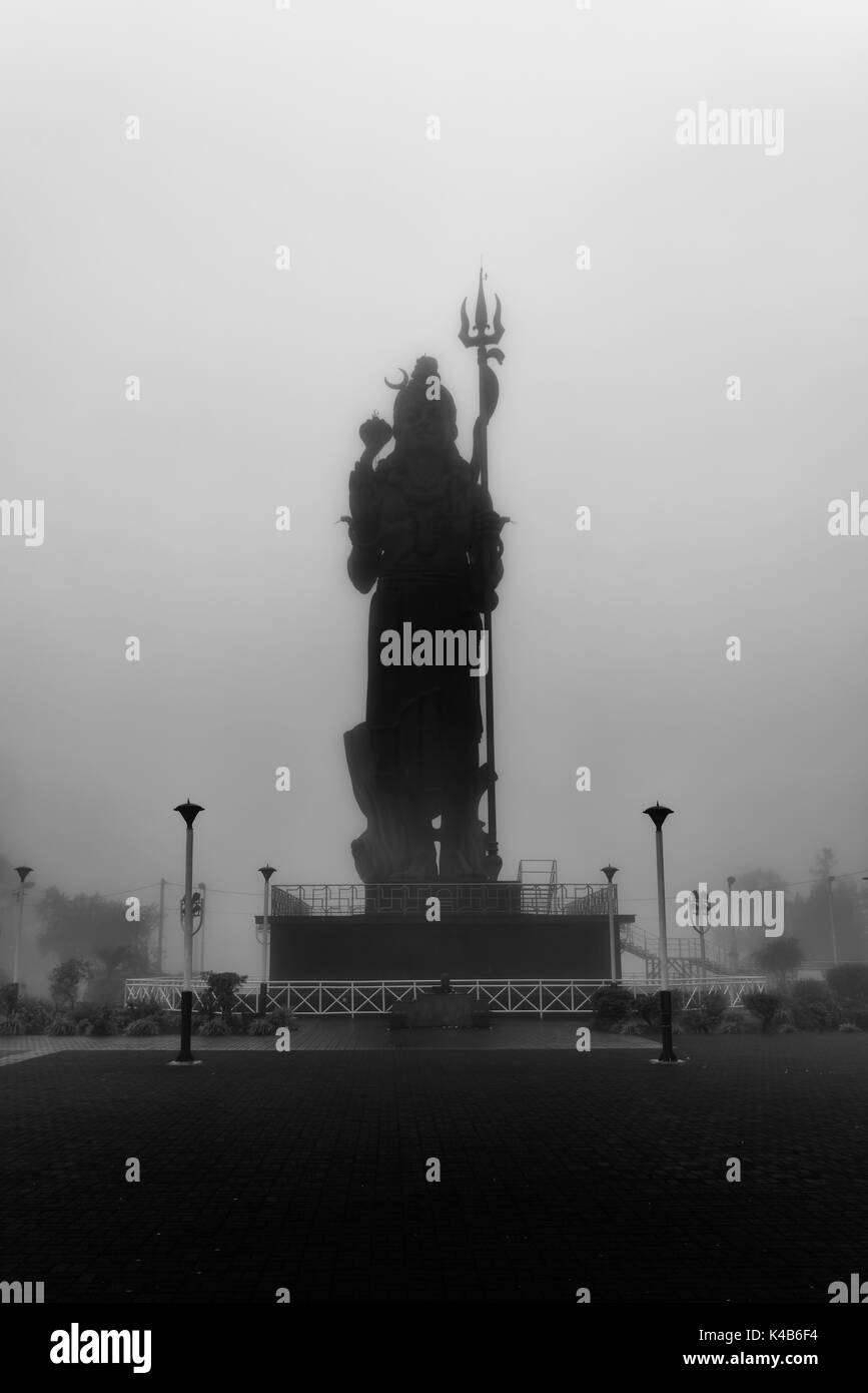 Black and white photo,shot  in a day with fog  for create a mystical feel, amazing statue of Lord Shiva (Mangal Mahadev) at Grand Bassin in Mauritius. - Stock Image