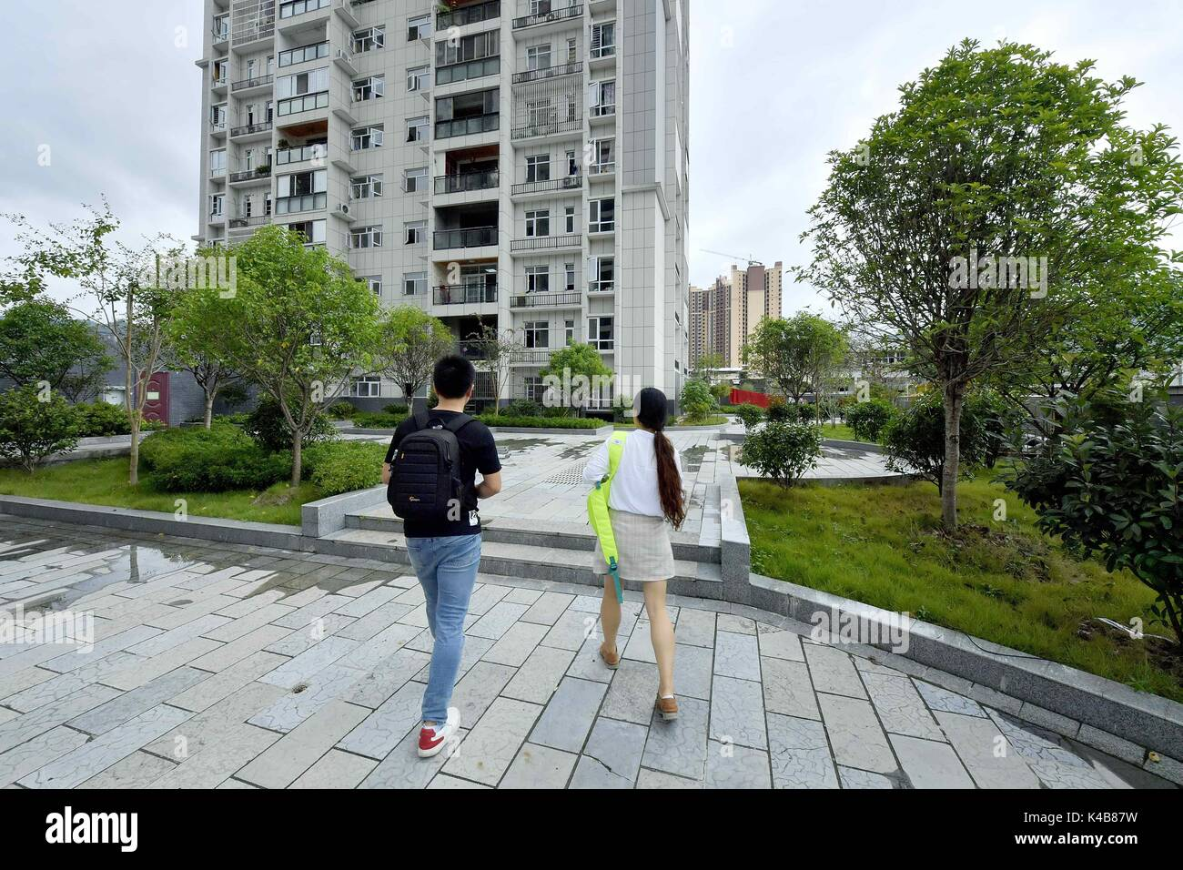Enshi. 5th Sep, 2017. People walk back to the apartments built for young talent in Xuan'en County of central China's Hubei Province, Sept. 5, 2017. 'Apartment for talents', apartment designed to attract talents to contribute to local development, has appeared in Xuan'en County recently. Credit: Song Wen/Xinhua/Alamy Live News - Stock Image