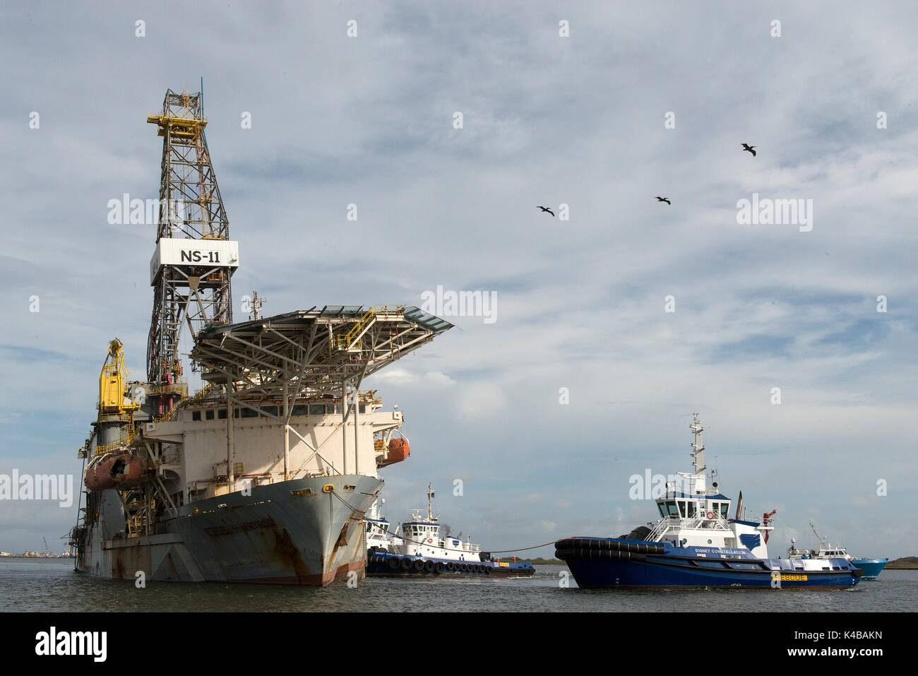 Rescue and salvage tug boats pull the grounded drill ship Paragon DPDS1 upright in the Aransas Pass shipping channel in the aftermath of Hurricane Harvey September 4, 2017 in Corpus Christi, Texas. The recovered vessel will be towed to Gulf Marine Fabricators and salvaged. - Stock Image