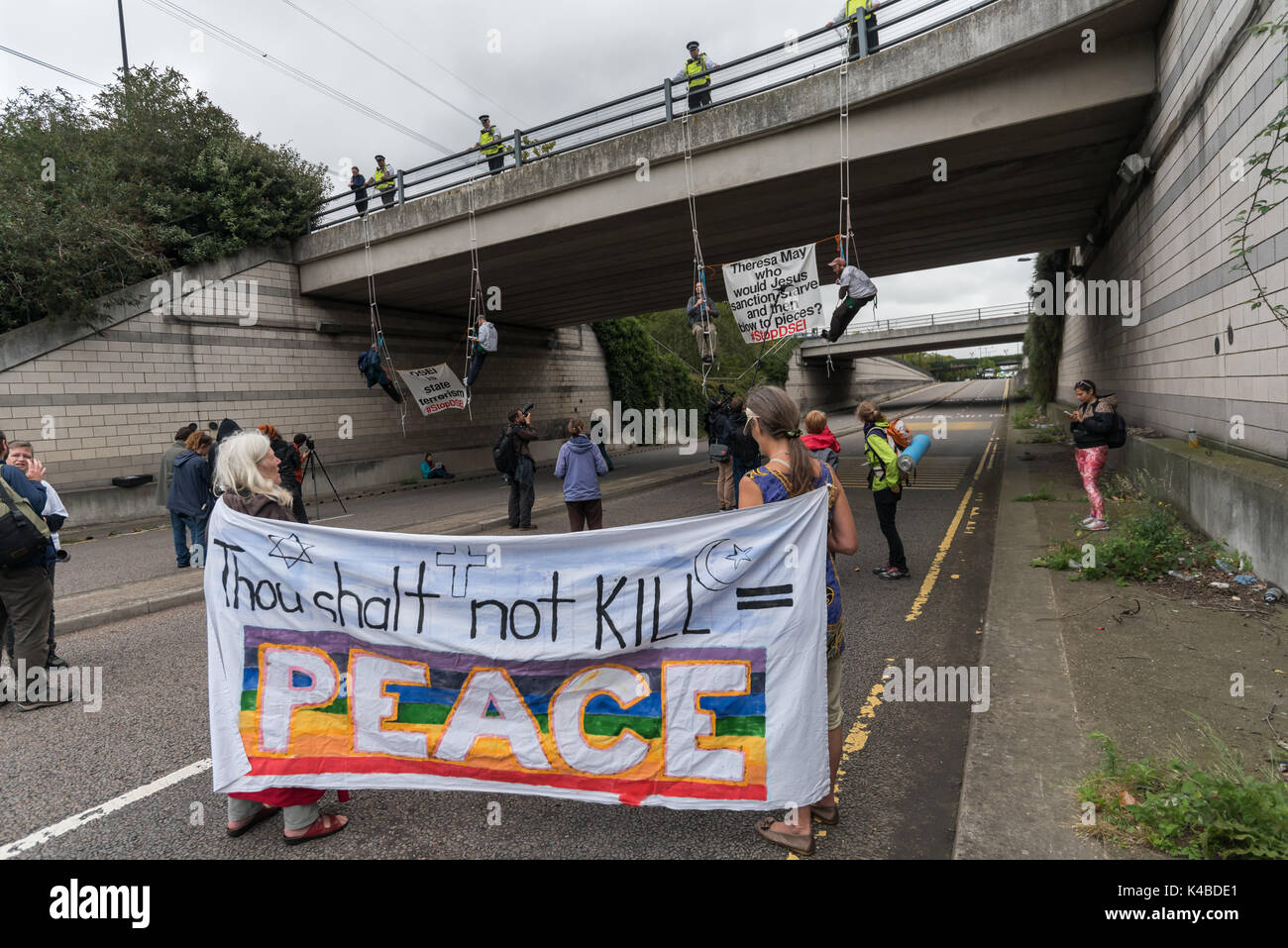 London, UK. 5th Sep, 2017. Protesters hang down on rope ladders from a bridge to block the road into the world's Stock Photo