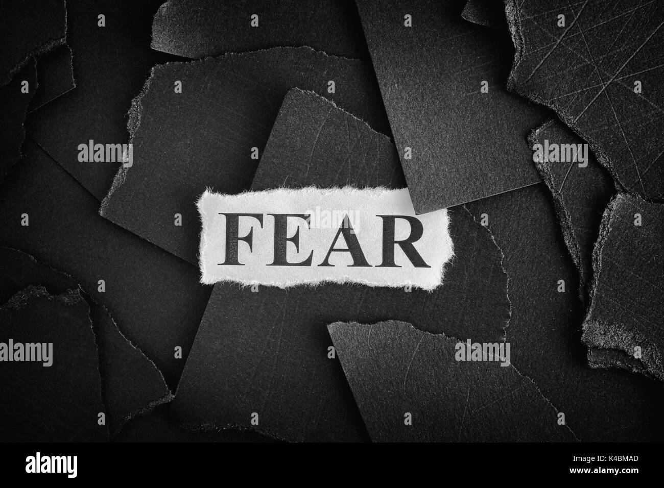 Fear. Torn pieces of black paper and word Fear. Concept Image. Black and White. Closeup. - Stock Image