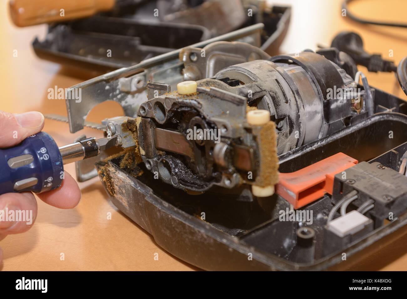 Handyman Repaired Broken Jigsaw With Screwdriver - Stock Image