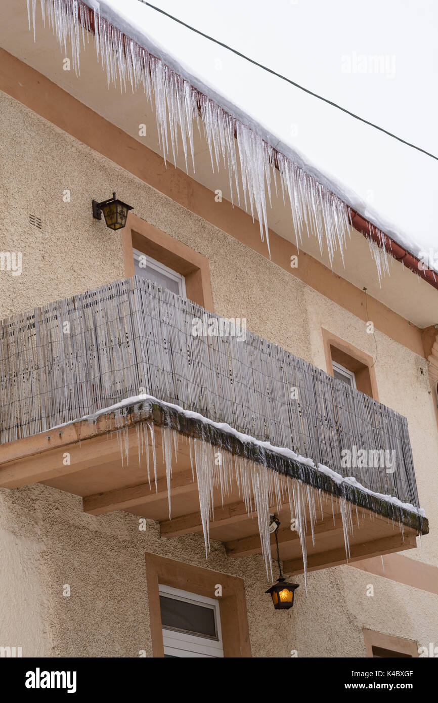 Large Icicles Hanging Idyllically From Several Floors Of A House - Stock Image