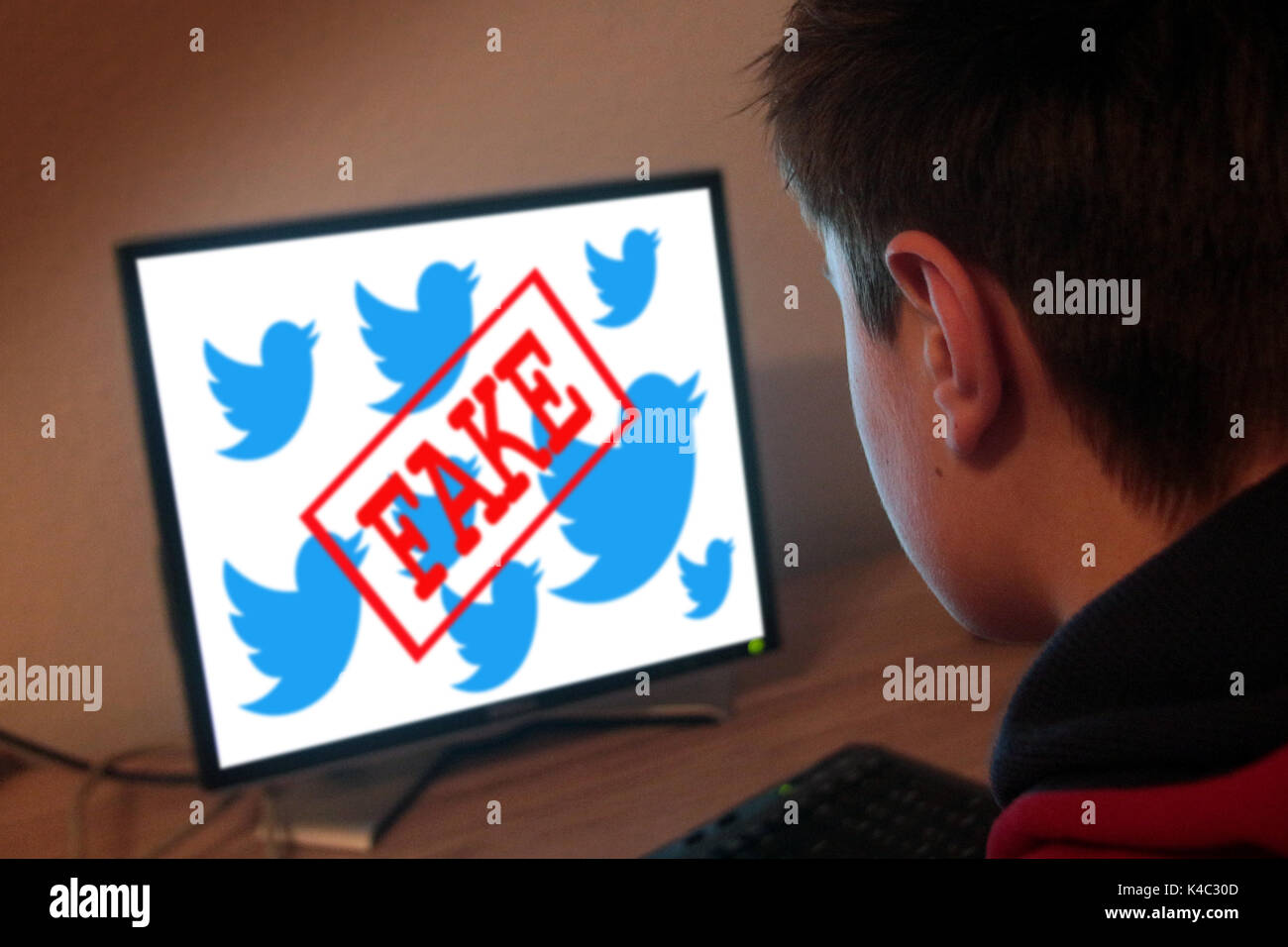 Young Man In Front Of A Computer With Word Fake Over Twitter Signs Stock Photo