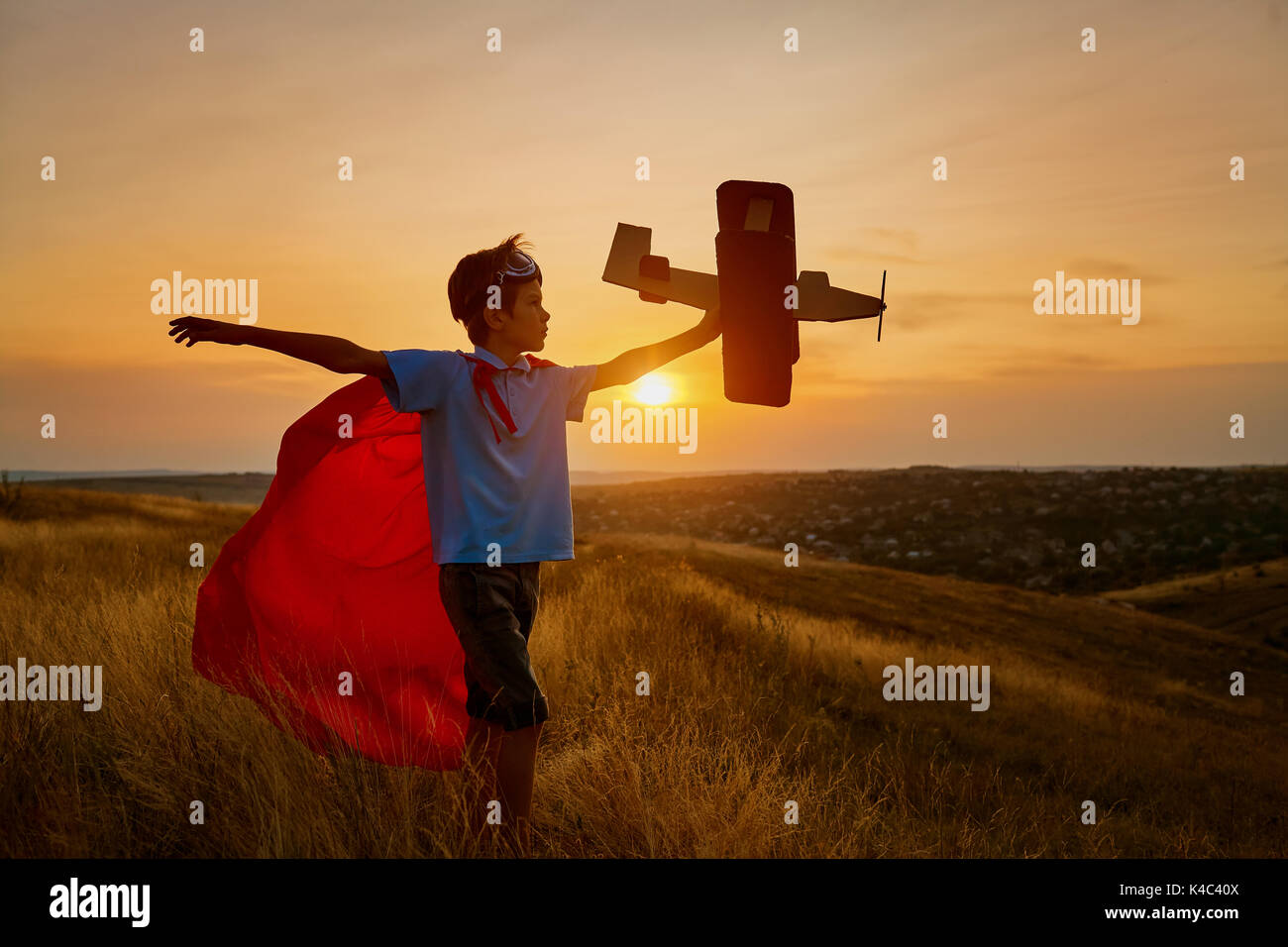 A happy boy in a superhero costume is playing with an airplane. - Stock Image