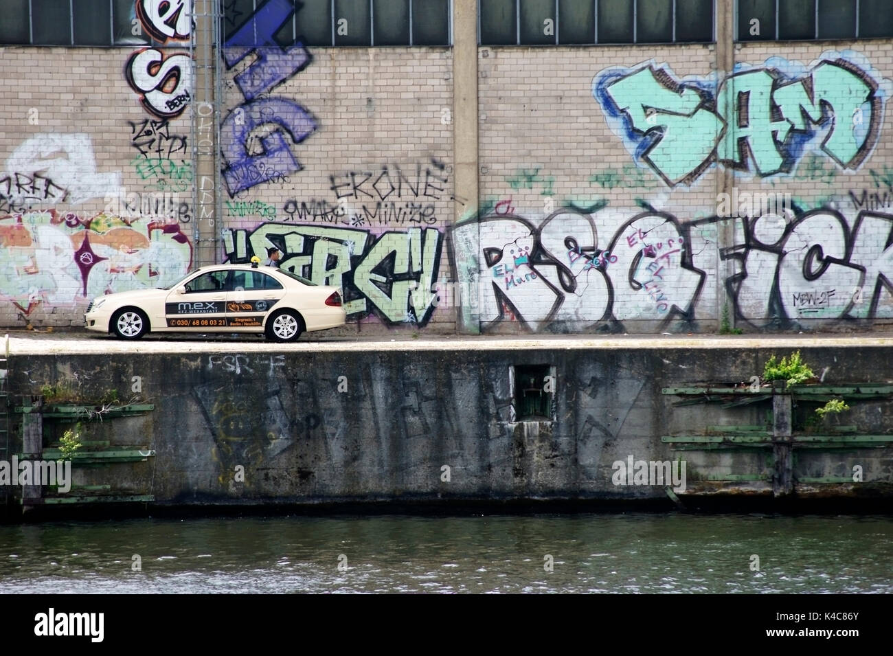 Taxi In Front Of Brightly Painted Graffiti Wall - Stock Image
