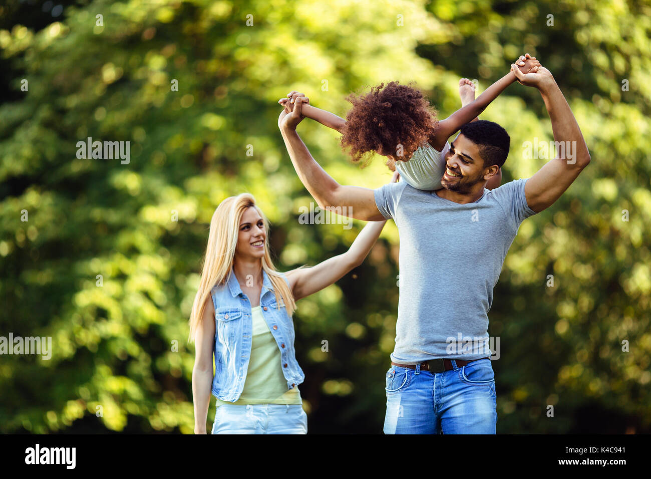 Picture of happy young couple spending time with their daughter - Stock Image