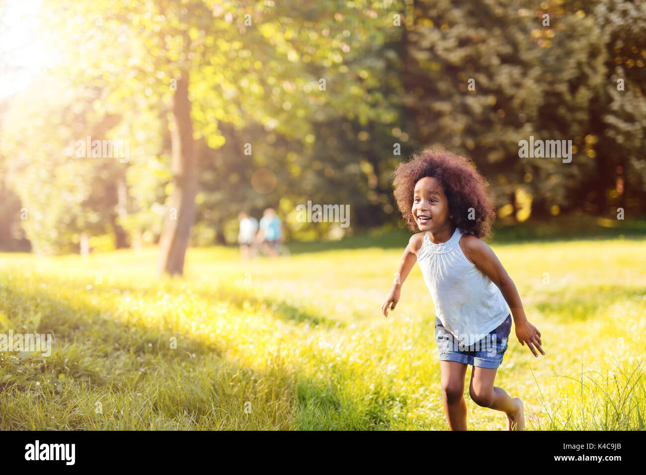 Portrait of happy little girl running on grass land Stock Photo