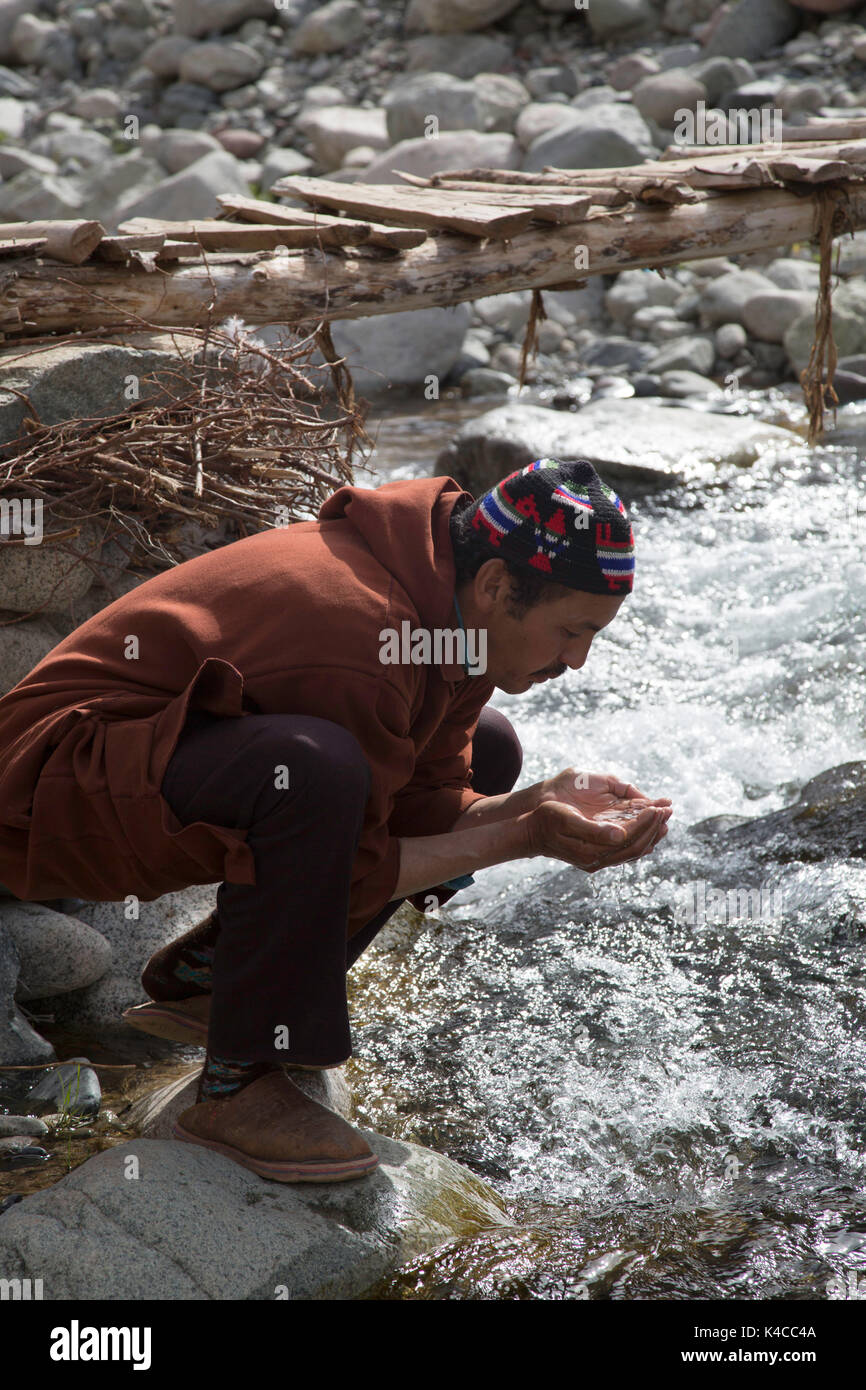 Berber man drinking from river, Setti Fatma market, Ourika valley, Morocco - Stock Image