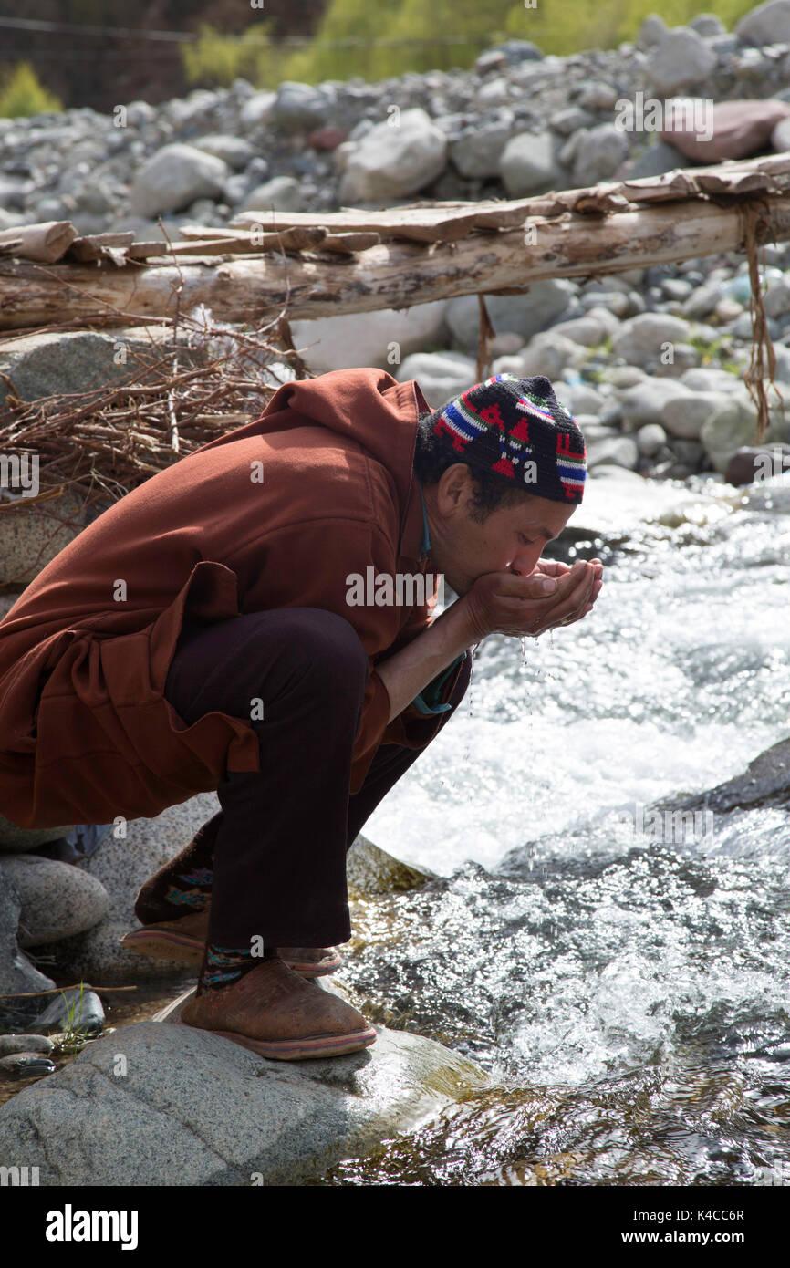 Berber man drinking from river, Setti Fatma market, Ourika valley, Morocco Stock Photo