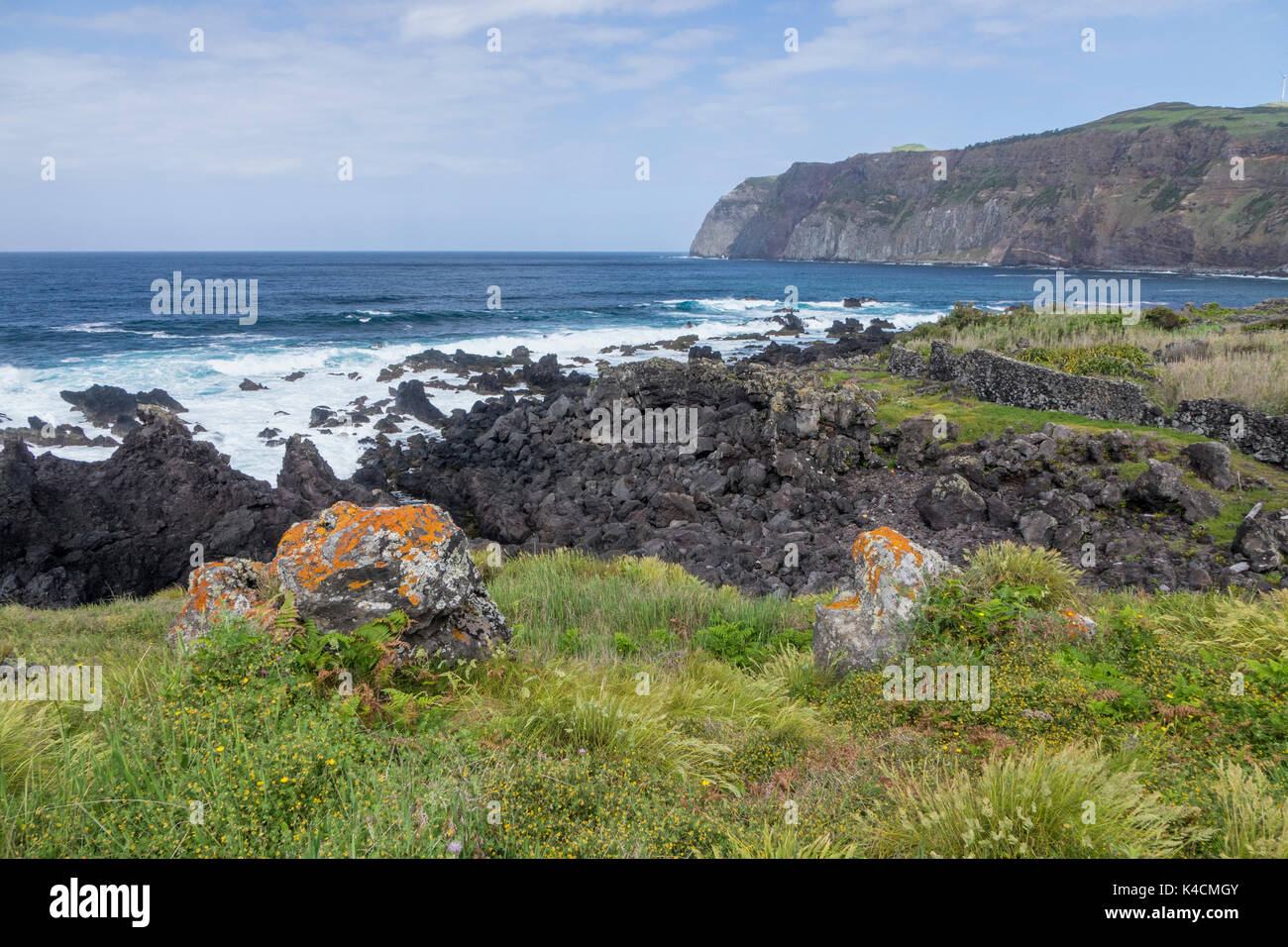Cliffline With Blue Atlantic And White Surge, In The Front Green Meadow And Volcanic Rocks. Graciosa, Azores - Stock Image