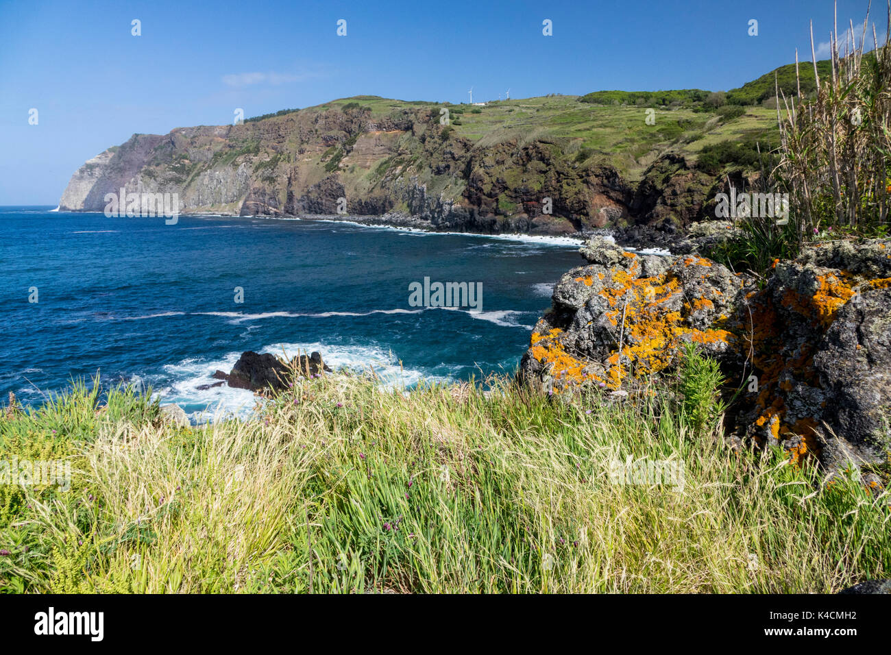 Cliffline With Blue Atlantic And White Surge, In The Front Green Meadow And Volcanic Rocks Overgrown With Lichen. Graciosa, Azores - Stock Image